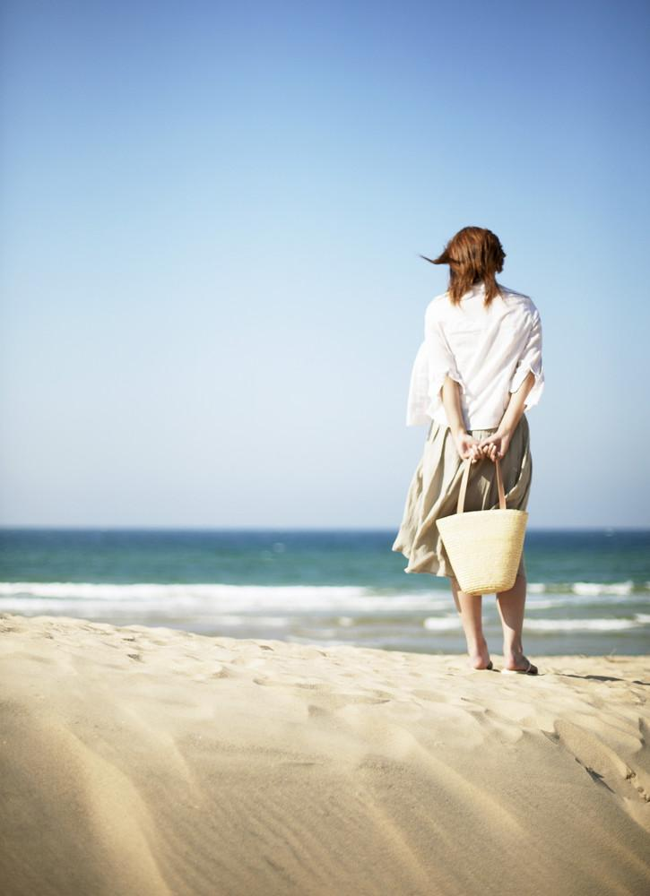 Woman on Beach Looking at Ocean